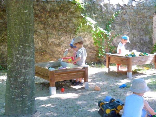 Enfants jouant avec un bac à sable surélevé
